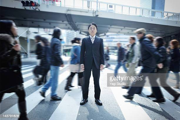 Businessman standing on a pedestrian crossing