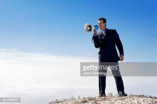Businessman Standing on a Sand Dune and Shouting Into a Megaphone : Bildbanksbilder