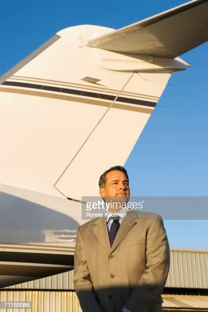 Businessman standing on airplane runway