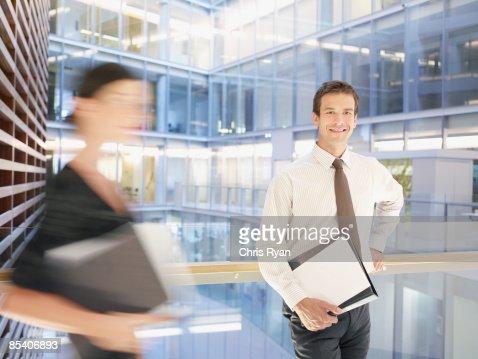 Businessman standing on atrium balcony : Stock Photo