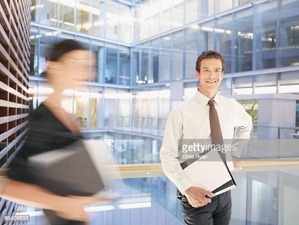 アトリウムのバルコニーに立っているビジネスマン