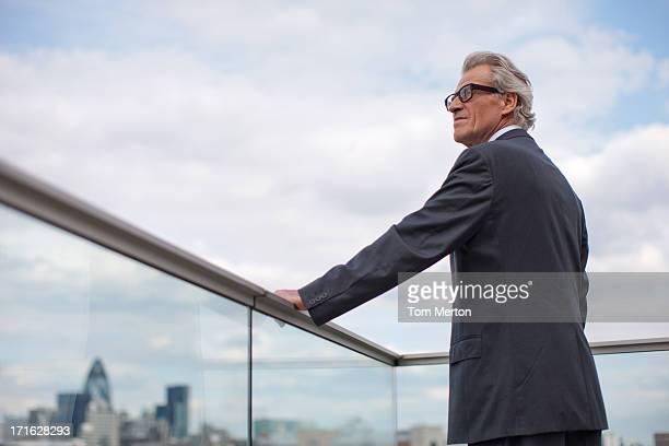 バルコニーの手すりに立っているビジネスマン