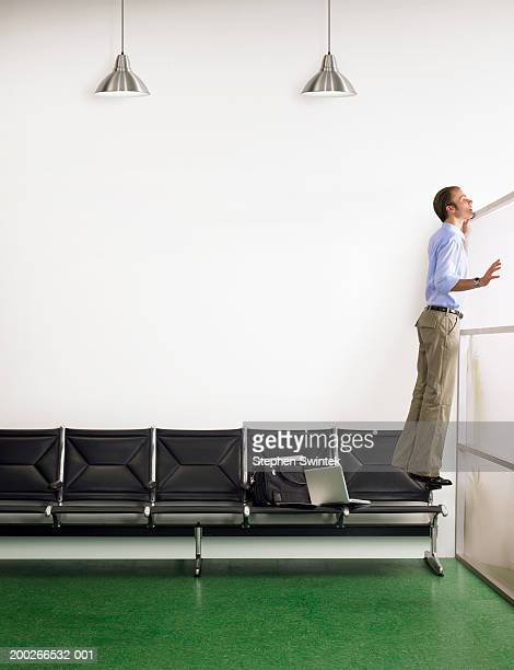 Businessman standing on chair, looking over waiting room divider