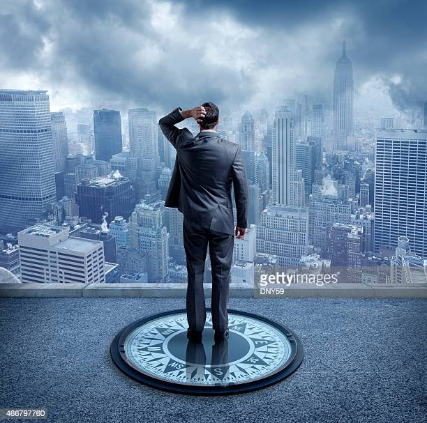 Businessman standing on compass looking at New York City