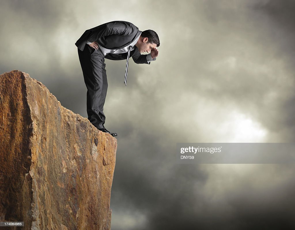 Businessman standing on edge of cliff looking down