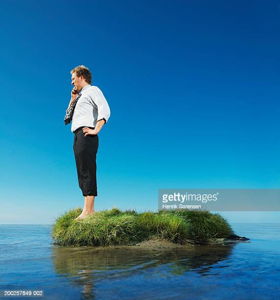 Businessman standing on grass island with hand on hip