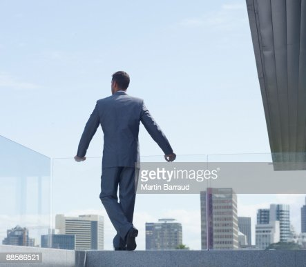 Businessman standing on highrise balcony : Stock Photo