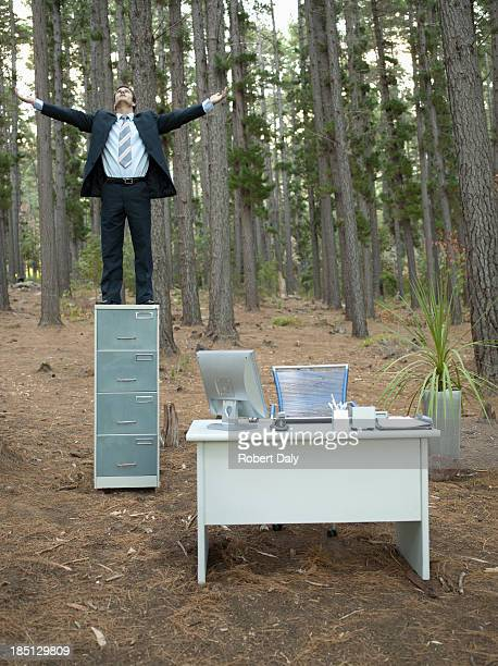 A businessman standing on his filing cabinet with arms outstretched in the woods