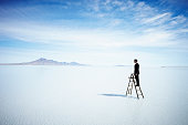 Businessman standing on ladder in lake