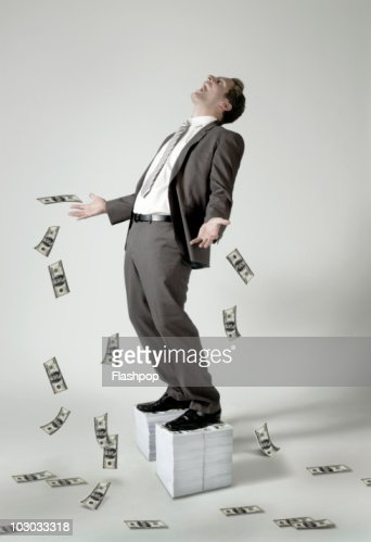 Businessman standing on large pile of dollar notes : Stock Photo