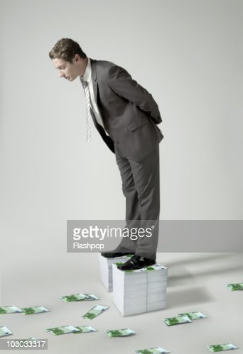 Businessman standing on large pile of Euro notes : Stock Photo