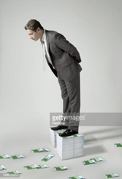 Businessman standing on large pile of Euro notes