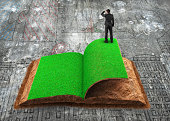Small businessman standing on the opened book of green grass and soil textured, on dirty doodles concrete floor background, concept of ECO, renewable energy and circular economy.