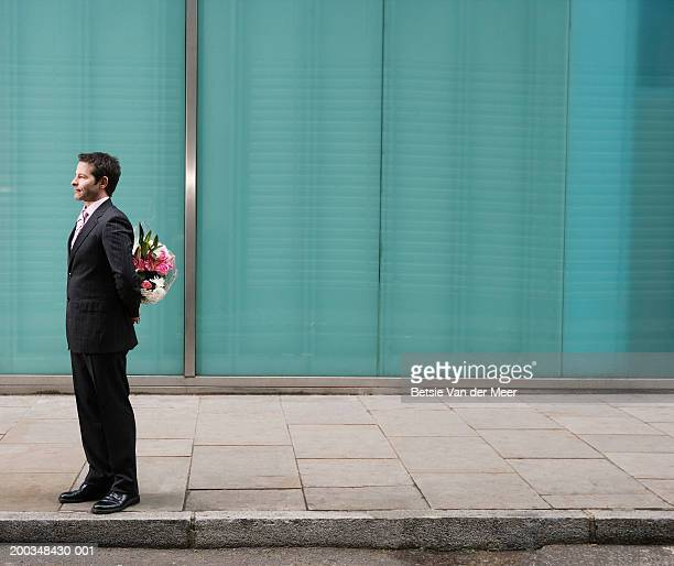 Businessman standing on pavement, bunch of flowers behind back