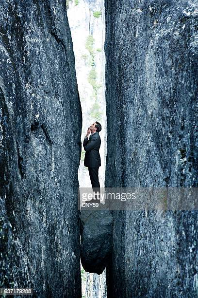 Businessman Standing On Rock Stuck In Deep Crevasse