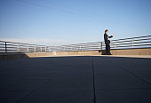 Businessman standing on roof of building, holding mobile phone