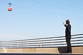Businessman standing on roof of building, holding up mobile phone