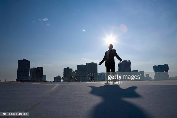 Businessman standing on runway with arms out, dusk, rear view