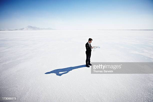 Businessman standing on salt flats looking at map