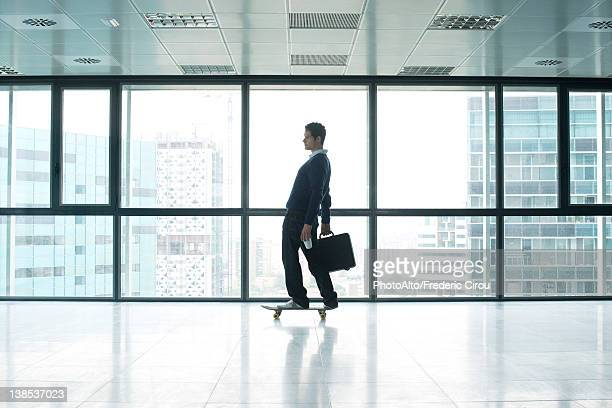 Businessman standing on skateboard with briefcase