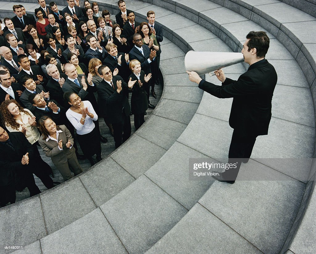 Businessman Standing on Steps Outside Talking Through a Megaphone, Large Group of Business People Listening and Applauding : Stock Photo