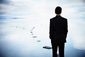 Businessman standing on stone pathway in water