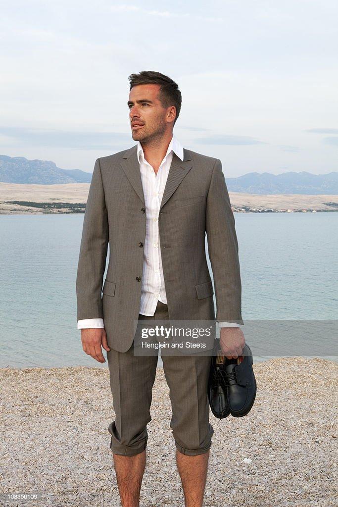 Businessman standing on the beach : Stock Photo
