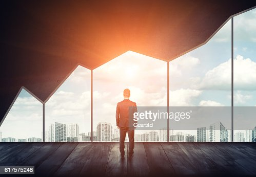 Businessman standing on the floor back to us looking through : Stock Photo