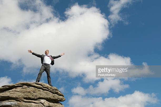 Businessman Standing on Top of Rock Arms Spead Blue Sky