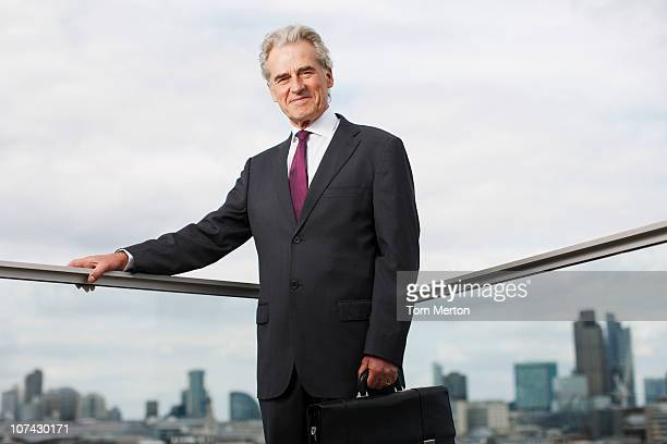 Businessman standing on urban balcony