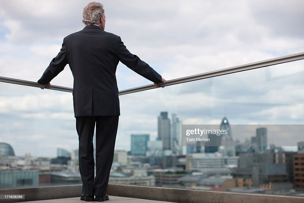 Businessman standing on urban balcony : Stock Photo