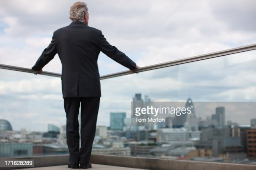 Businessman standing on urban balcony