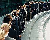 Businessman Standing Out in a Line of Business People Waiting Outdoors on a Step