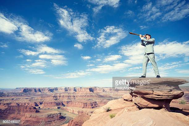 Hombre de negocios de pie al aire libre en Mesa paisaje con telescópica