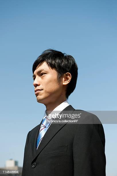 Businessman standing outdoors, Tokyo Prefecture, Honshu, Japan
