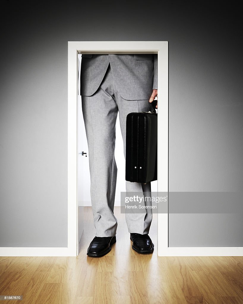 Businessman standing outside a very small door. : Stock Photo