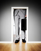 Businessman standing outside a very small door.