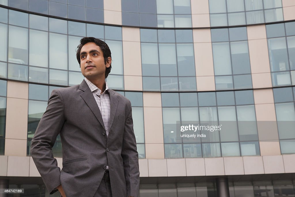 Businessman standing outside an office building : Stock Photo