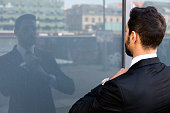 handsome businessman standing outside and looking at his reflection in a window
