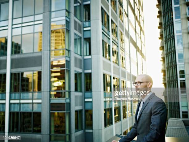 Businessman standing outside buildings behind