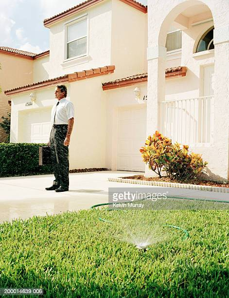 Businessman standing outside house
