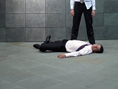 Businessman standing over colleague lying on pavement