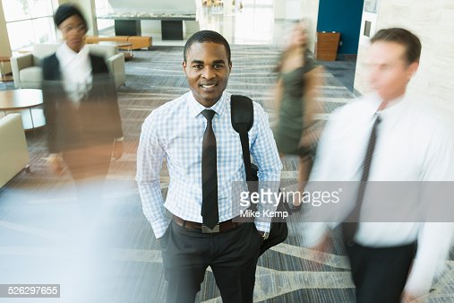 Businessman standing still in busy office lobby