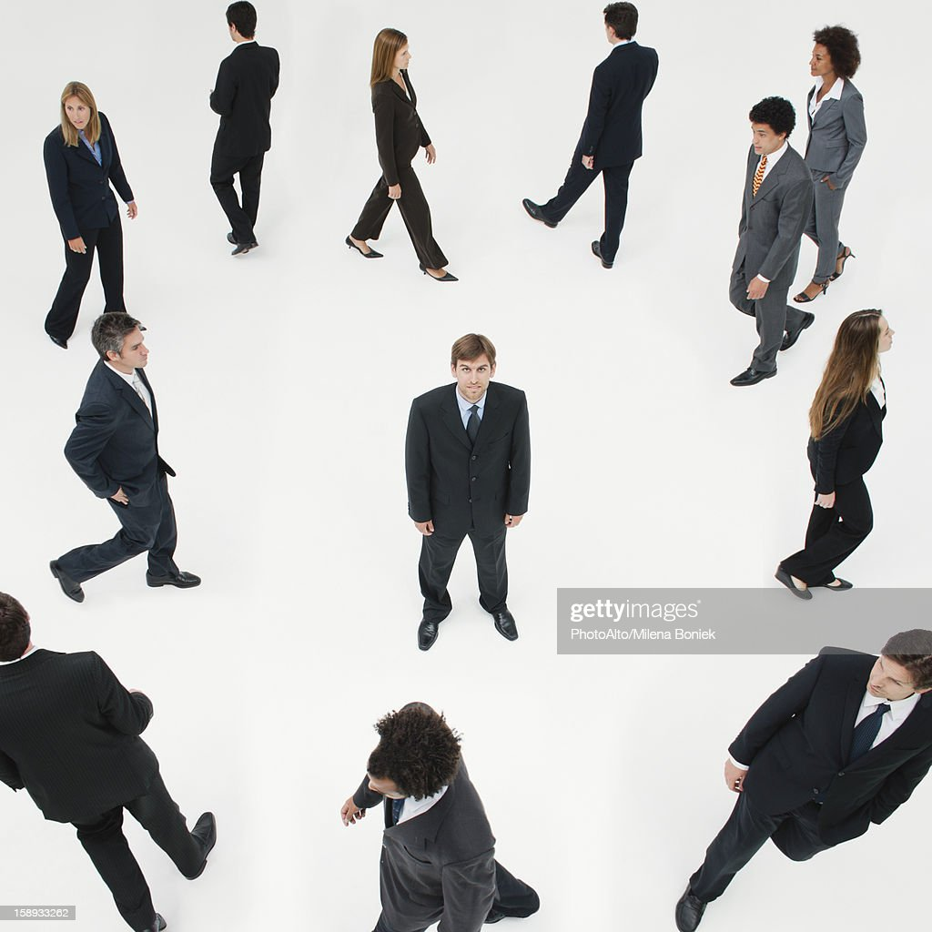 Businessman standing still in midst of other business professionals on the move : Stock Photo