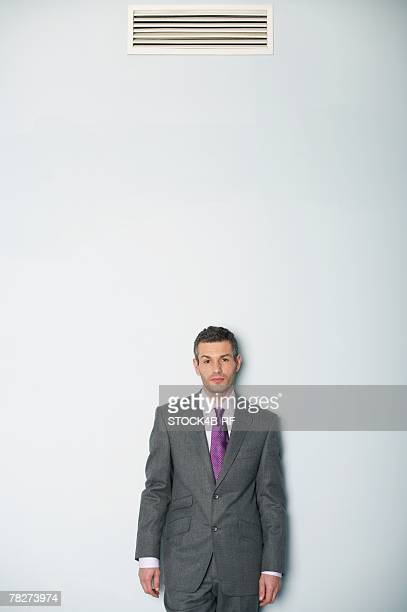Businessman standing under air conditioner