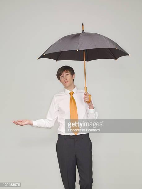 businessman standing under an umbrella