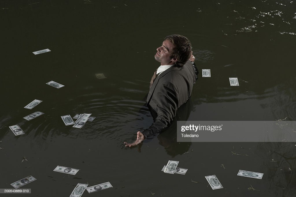 Businessman standing waist deep in water surrounded by floating money : Stock Photo
