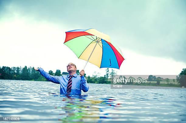 Geschäftsmann stehend Taille in Wasser mit Regenschirm