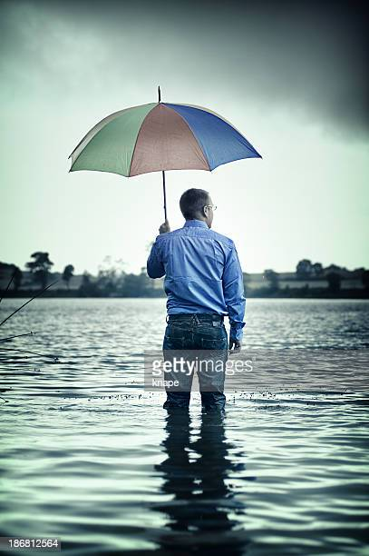Businessman standing waist up in water with a umbrella