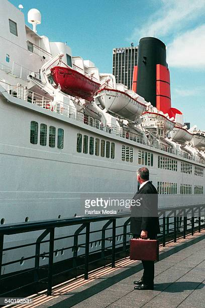 Businessman standing with a briefcase overlooking a ship at the dock